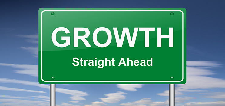 Image of green highway sign reading growth straight ahead