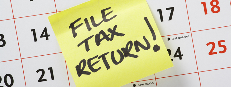 calendar image with post-it note and handwritten reminder to file tax return