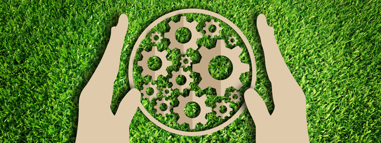 paper cut-out of gears in a circle held by two hands on a green grassy background denoting environmentally friendly practices