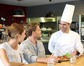 Photo of man in chef hat serving food to man and woman