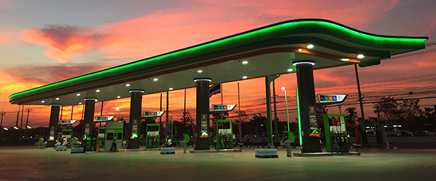 image of gas pumps outside of convenience store at night
