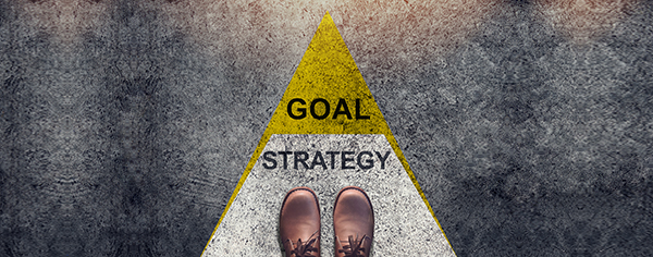 image looking down at feet on a road that says strategy and goal with an arrow pointing forward